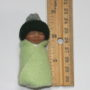 green baby doll bundle next to ruler