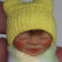 baby doll with yellow hat face close up