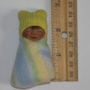 Miniature baby doll next to ruler