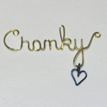 Cranky written in brass wire with purple dangling heart