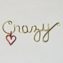 crazy written in wire with red dangling heart