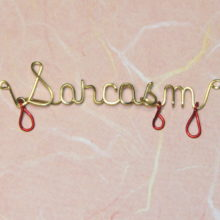 Sarcasm wirtten in brass wire with red drips