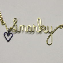 snarky written in wire with dangling purple heart