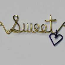 Sweet written in brass wire with a dangling heart