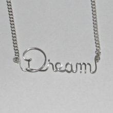 the word dream written in sterling silver wire